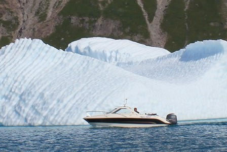 A small private boat saling near an iceberg