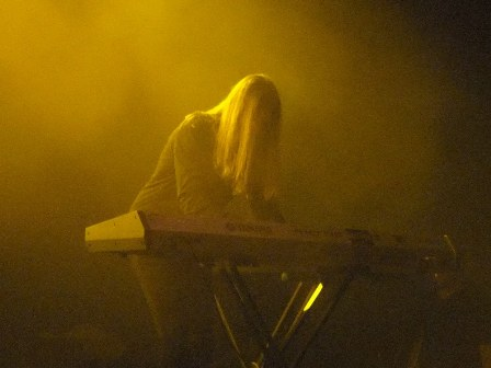 Oliver Palotai playing keyboards under a yellow light in Budapest