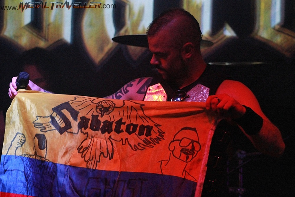Joakim Bodén holding the flag of Colombia that Sabaton fans made for them