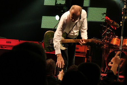 Francis Rossi giving a Status Quo guitar pick to a fan on the first row