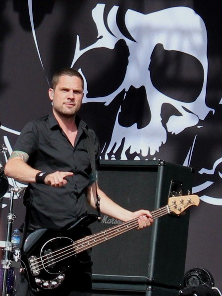 Anders Kjølholm playing bass with Volbeat